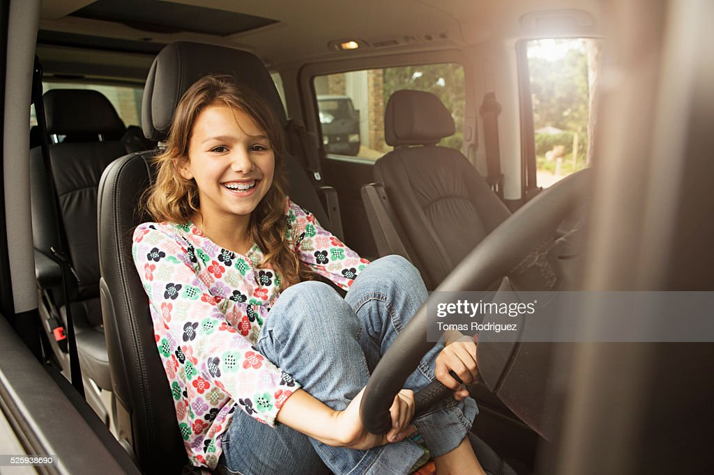Girl (8-9) sitting in car and holding steering wheel : Stockfoto