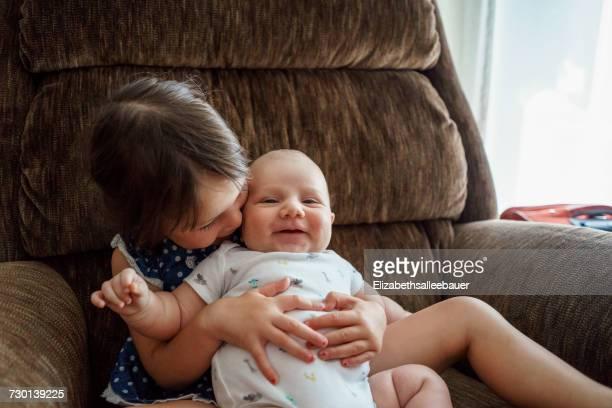 Girl sitting in chair cuddling a baby boy