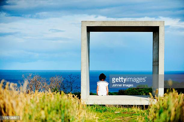 Girl sitting in concrete square and looking at sea