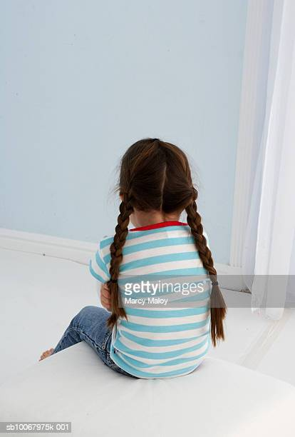 Girl (4-5) sitting in corner, rear view