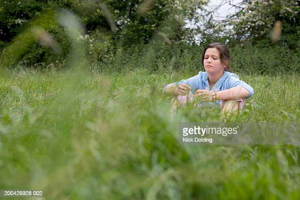 Girl (11-13) sitting in field, ground view