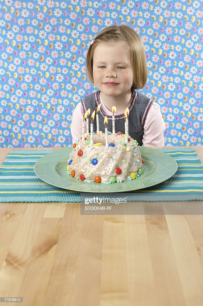 Girl sitting in front of a Birthday cake : Photo