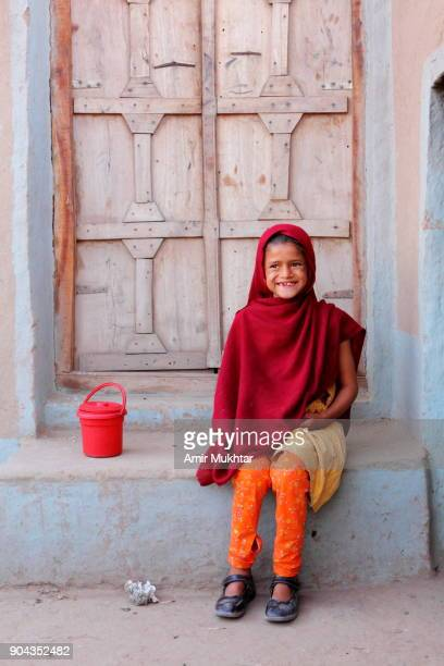 girl sitting in front of a door - pakistan girl stock photos and pictures