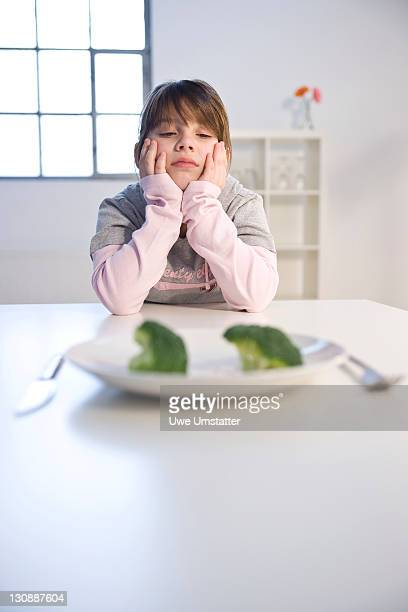 Girl sitting in front of a plate with broccoli in disgust