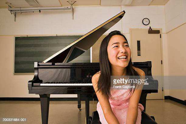 Girl (10-12) sitting in front of piano in classroom, smiling