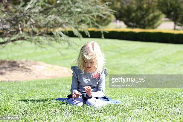 Girl sitting in garden playing with grass