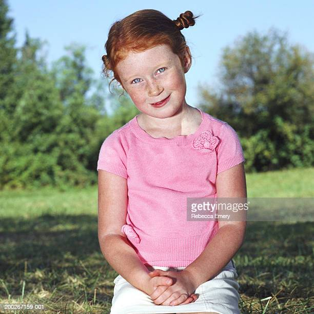 girl (5-7) sitting in grass with hands folded, smiling, portrait - emery stock photos and pictures