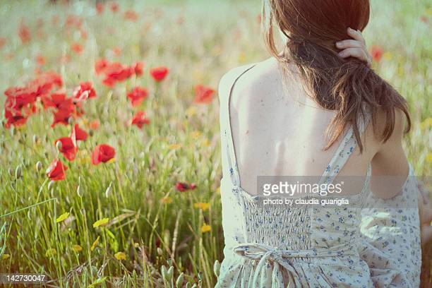 Girl sitting in green field with poppies