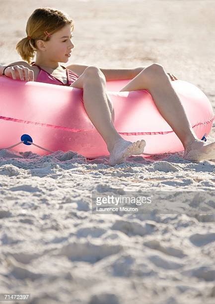 girl sitting in inner tube on beach - pink tube photos et images de collection