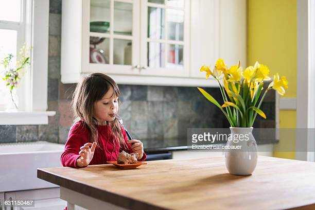 girl sitting in kitchen eating chocolate dessert - solo una bambina femmina foto e immagini stock