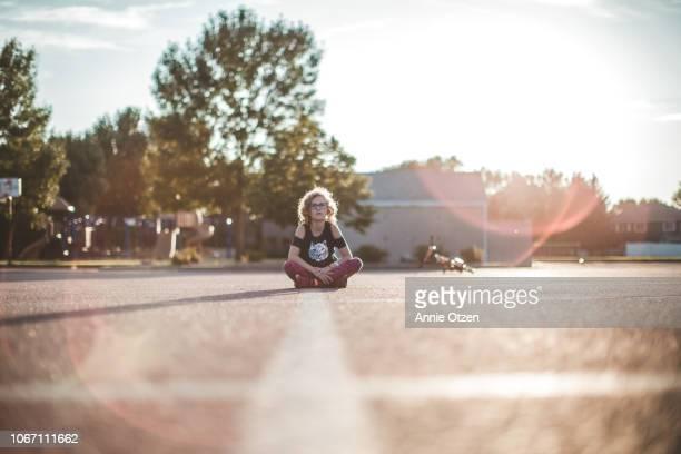 girl sitting in middle of parking lot - al centro foto e immagini stock