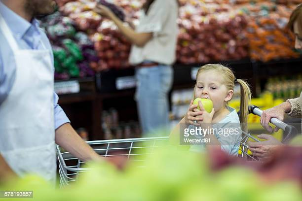 Girl sitting in shopping trolley eating apple