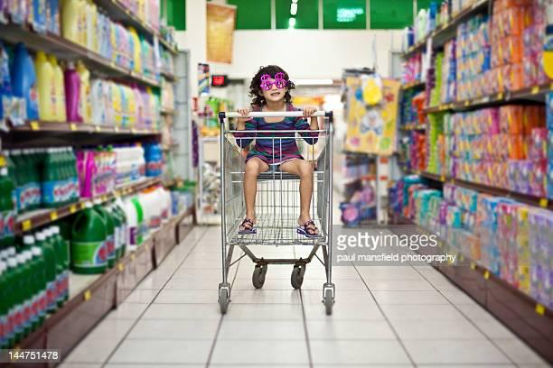 Girl sitting in shopping trolley