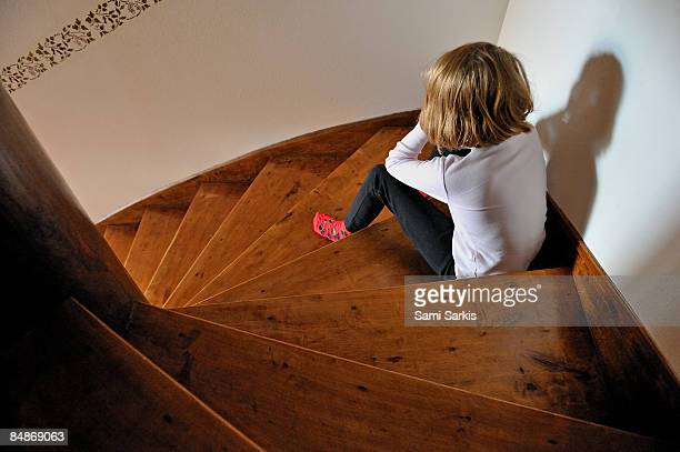 Girl (8) sitting in staircase corner, pouting