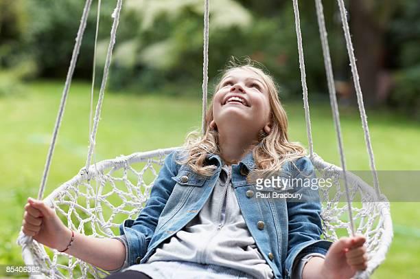 Mädchen sitzend auf Schaukel im Garten