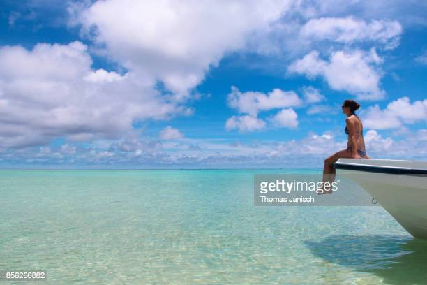 Girl sitting in the front of a motorboat looking at the blue ocean
