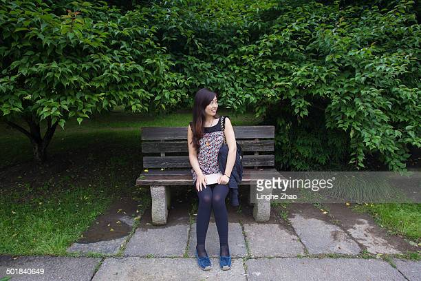 Girl sitting in the wooden bench