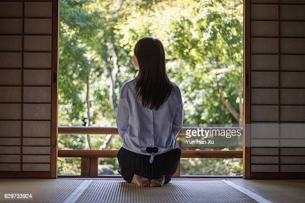 Girl Sitting in Traditional Japanese House Looking Out