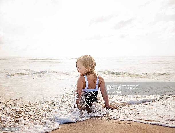 Girl (4-5) sitting in water on beach