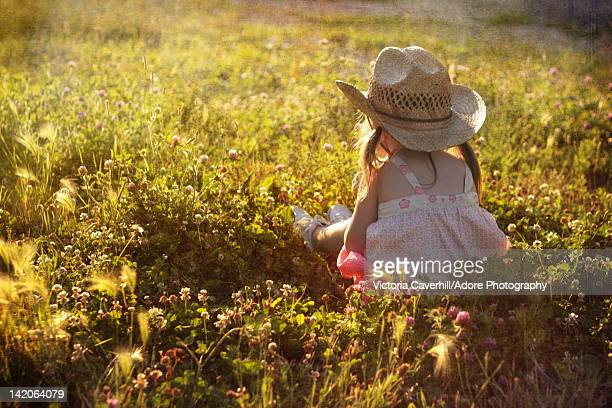 Girl sitting in wild flower field