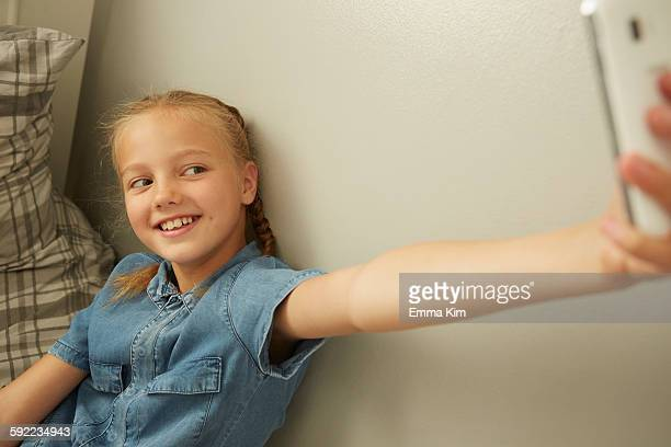 Girl sitting leaning against wall using smartphone to take selfie smiling
