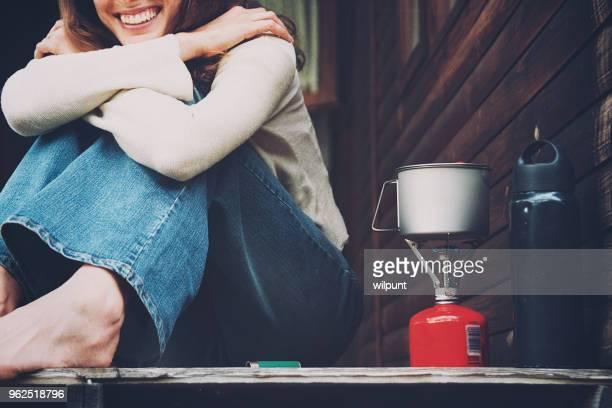 Jeune fille assise à côté de la bouillante réchaud de camping