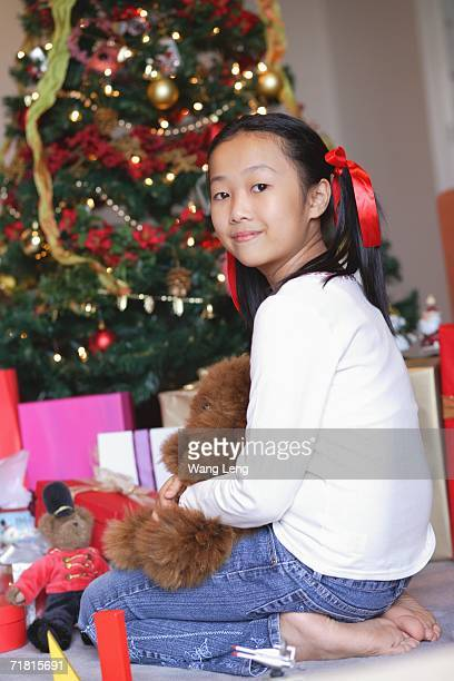 Girl sitting next to Christmas tree, holding teddy bear, looking at camera