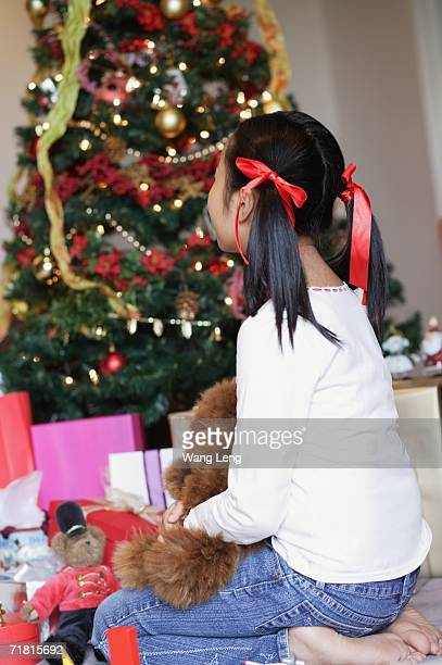 Girl sitting next to Christmas tree, rear view