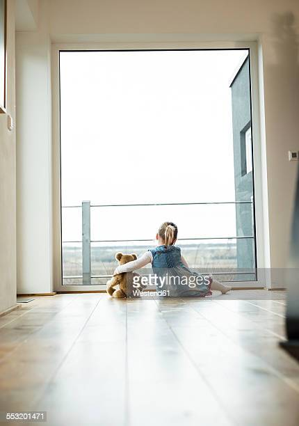 Girl sitting next to teddy looking out of window