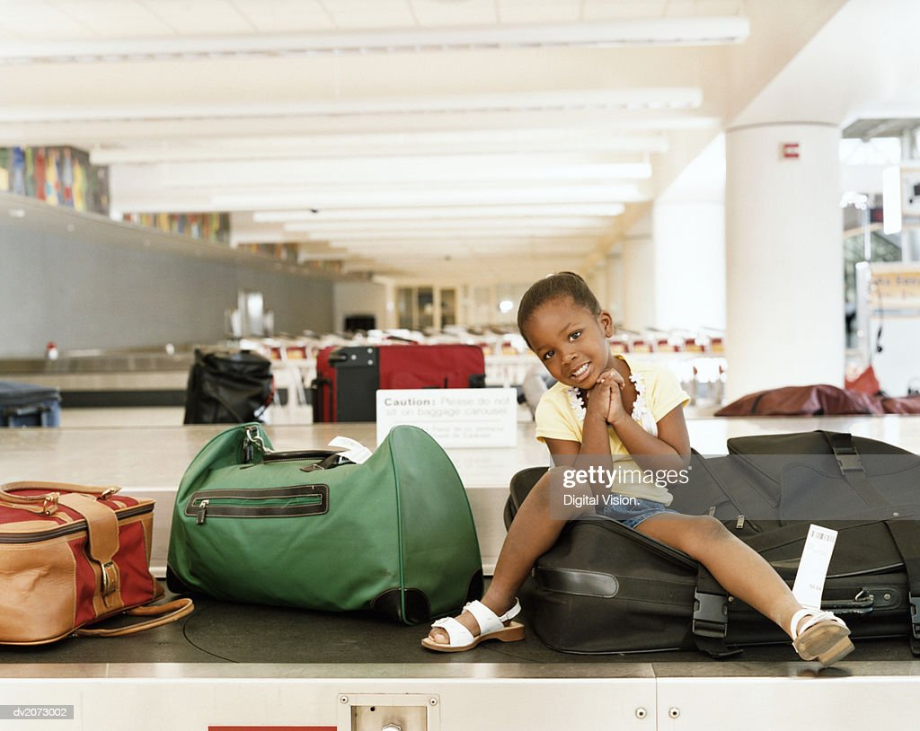 Girl Sitting on a Baggage Conveyor Belt in an Airport : Stock Photo