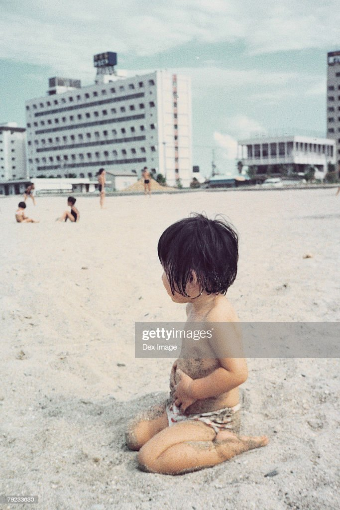 Girl sitting on a beach : Stock Photo