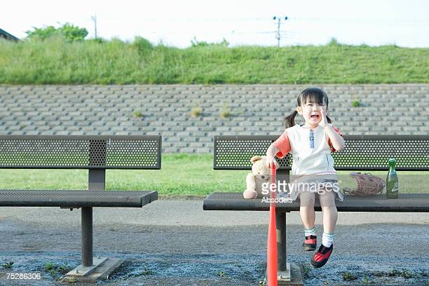 A girl sitting on a bench holding a bat