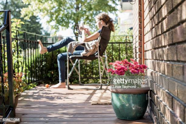 Girl sitting on a chair on a balcony reading a book