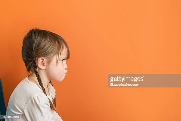 Girl sitting on a chair pouting