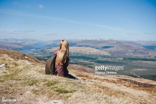 Girl sitting on a cliff and looking at the mountains.