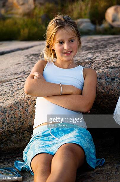 a girl sitting on a cliff by the sea. - little girls up skirt fotografías e imágenes de stock