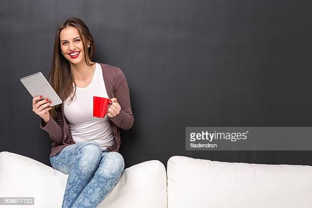 Mädchen sitzt auf einem Sofa mit tablet