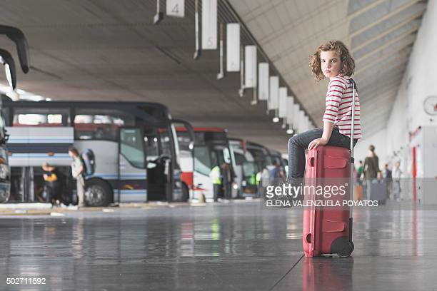 Girl sitting on a red suitcase