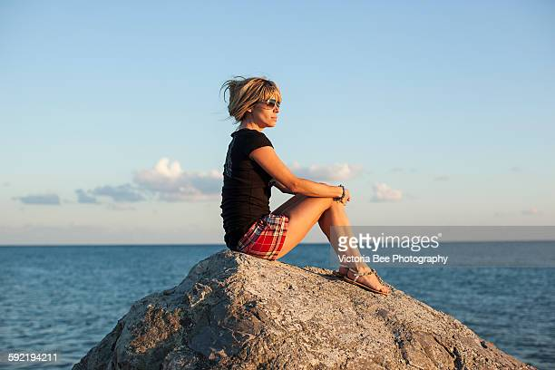 Girl sitting on a rock against the sea