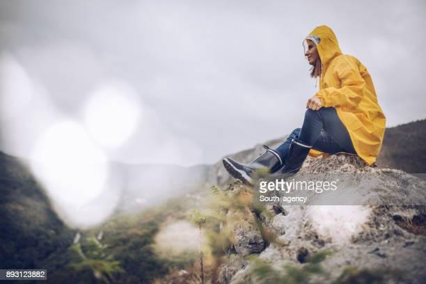 meisje zittend op een rots - rubberlaars stockfoto's en -beelden
