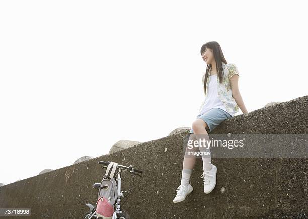 girl sitting on a seawall - 防波堤 ストックフォトと画像