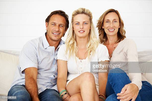 Mädchen sitzt auf einem sofa mit ihren Eltern
