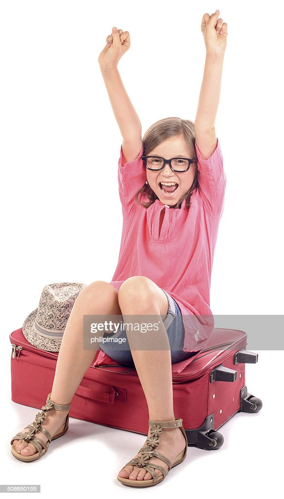 girl sitting on a suitcase is happy : Stock Photo