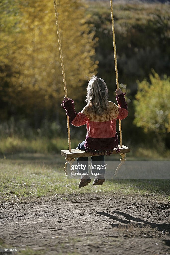 Girl sitting on a swing : Stockfoto