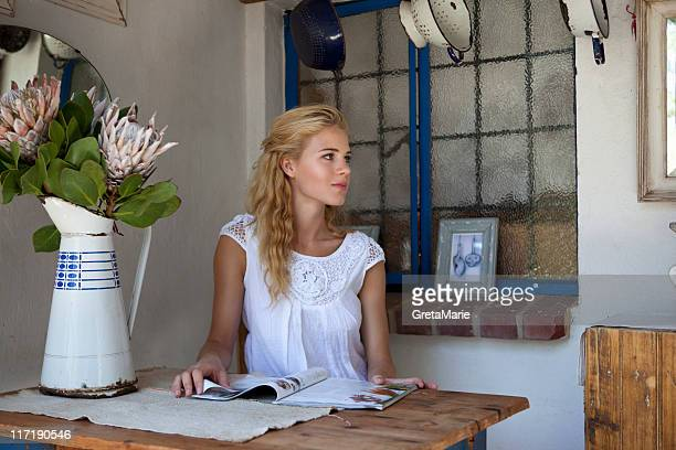 girl sitting on a table reading magazine - nature magazine stock pictures, royalty-free photos & images
