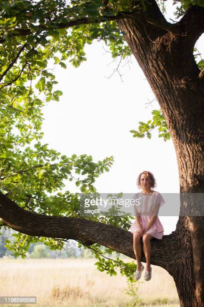 girl sitting on a tree - legs and short skirt sitting down stock pictures, royalty-free photos & images