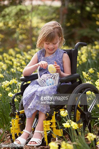 Girl sitting on a wheelchair and holding a basket of Easter eggs