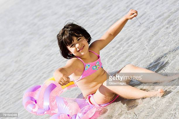 Girl sitting on an inflatable ring on the beach
