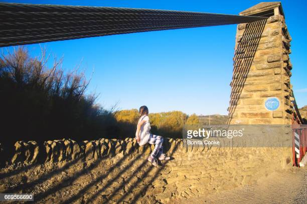 Girl sitting on and exploring the historic suspension bridge, Central Otago