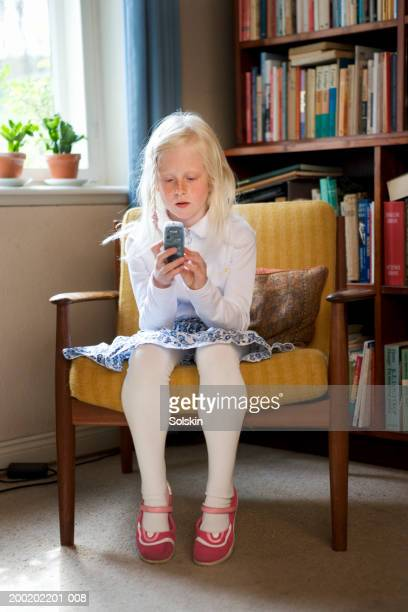 girl (8-10) sitting on armchair using mobile phone - little girls up skirt fotografías e imágenes de stock
